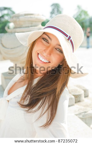 Portrait of pretty cheerful woman wearing white dress and straw hat in sunny warm weather day. Walking at summer park and smiling - stock photo