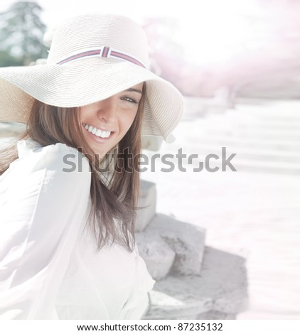 Portrait of pretty cheerful woman wearing white dress and straw hat in sunny warm weather day. Walking at summer park and smiling. Lots of copyspace - stock photo