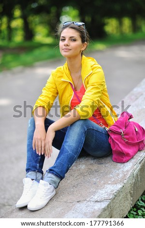Portrait of pretty cheerful young girl in a park - stock photo