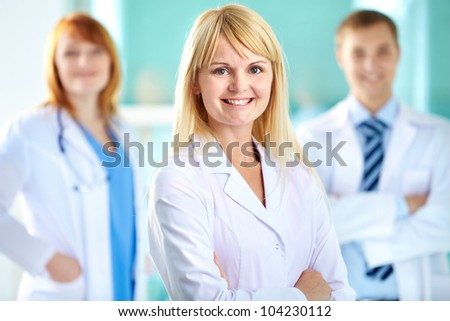 Portrait of pretty clinician in white coat looking at camera with smile - stock photo