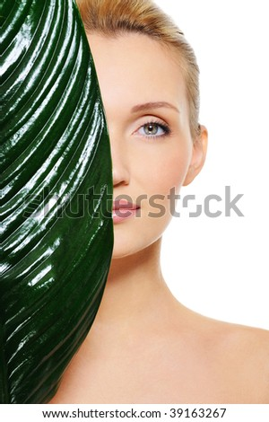 Portrait of pretty face of woman hiding behind the big green leaf - stock photo