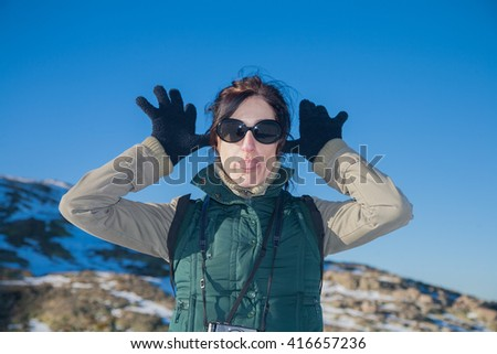portrait of pretty face woman with green vest and sunglasses looking gesturing hands gloves, making fun scoff and sticking out tongue, in winter outdoor blue sky