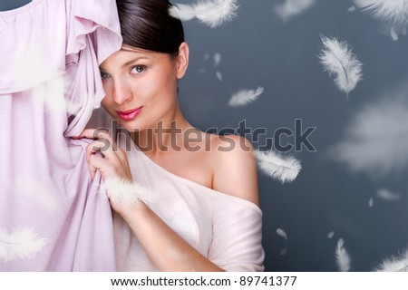 Portrait of pretty fashionable woman trying new clothes. Fashion poster shot indoors at studio. Lots of feathers around. Soft textile concept - stock photo