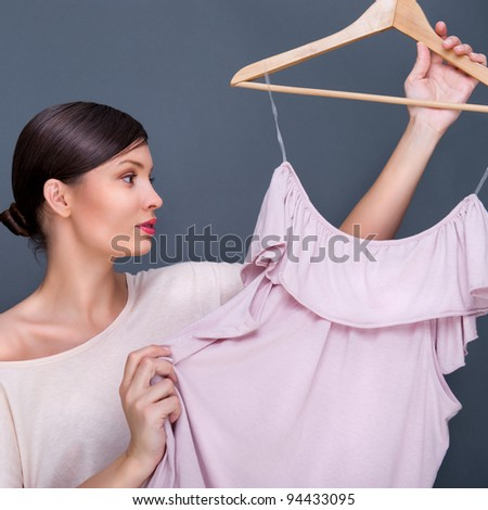 Portrait of pretty fashionable woman trying new clothes. Fashion poster shot indoors at studio against grey background. - stock photo