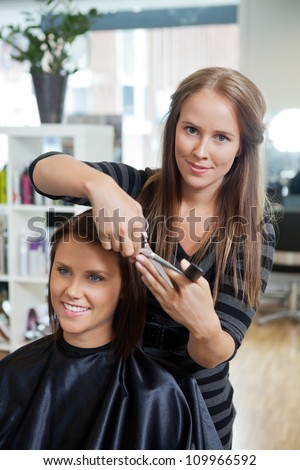 Portrait of pretty female beautician cutting hair of customer at parlor - stock photo