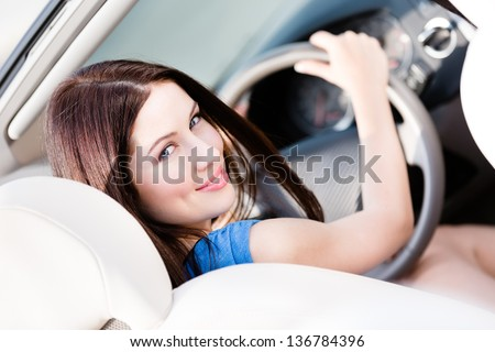 Portrait of pretty female driver turning back - stock photo
