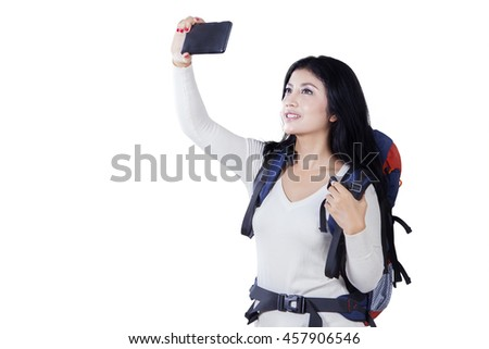 Portrait of pretty female traveler using smartphone to take selfie photo in the studio, isolated on white background