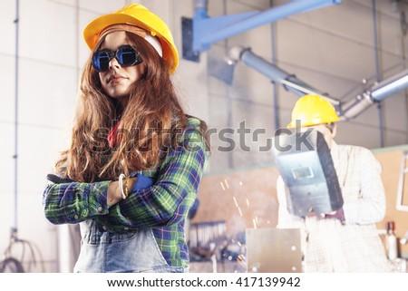 portrait of pretty female worker in a steel mill - stock photo