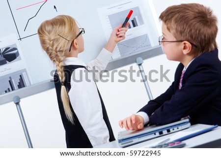 Portrait of pretty girl by the board and serious boy at workplace - stock photo