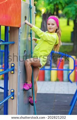 portrait of pretty girl doing rock climbing on playground - stock photo