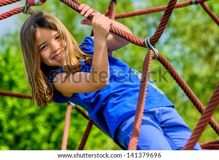 portrait of pretty girl doing rock climbing  with greenery in the background - stock photo