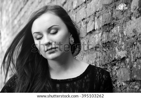 Portrait of pretty girl dreaming with closed eyes. Elegant young lady is lost in thought with flying hair in black and white.