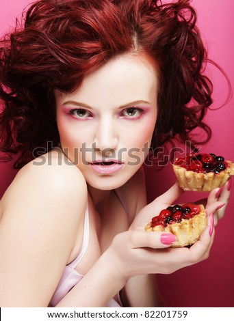 Portrait of pretty girl eating cake, close up. Pink background.