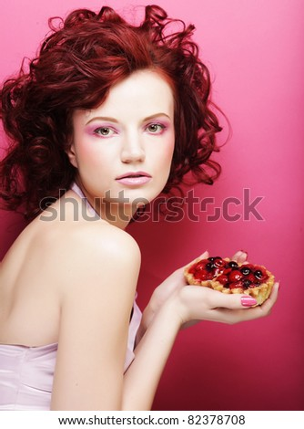 Portrait of pretty girl eating cake, close up. Pink background. - stock photo