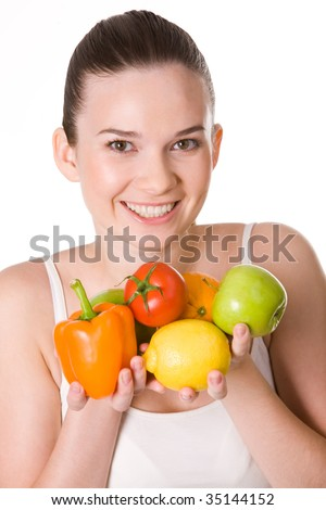 Portrait of pretty girl holding different fruits and vegetables in hands