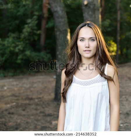 Portrait of pretty girl in forest, toned and noise added. - stock photo