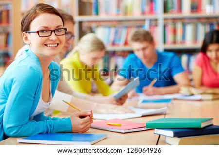 Portrait of pretty girl sitting in college library and looking at camera - stock photo