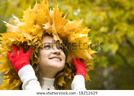 Portrait of pretty girl wearing maple wreath and touching it by hands