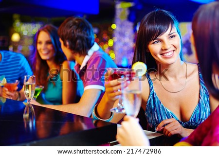 Portrait of pretty girl with cocktail talking to her friend in bar