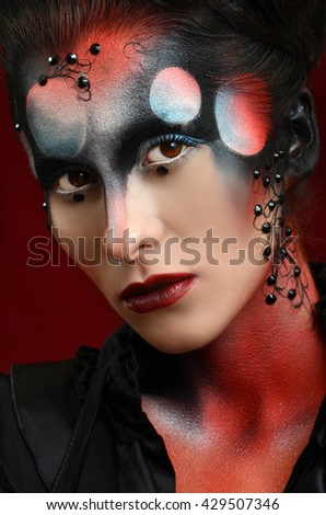 Portrait of pretty girl with creative art makeup painted different colors