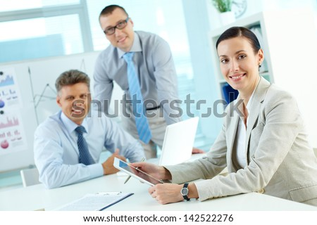 Portrait of pretty lady looking at camera in working environment in office - stock photo