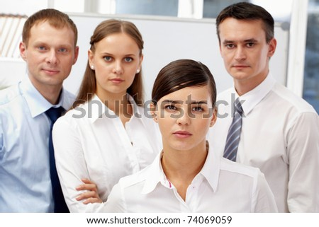 Portrait of pretty leader looking at camera with three employees behind - stock photo