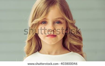 Portrait of pretty little blonde girl with beautiful big eyes looking at camera - stock photo