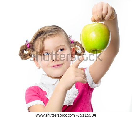 portrait of  pretty little girl holding green apple isolated on white studio shot looking pointing at apple - stock photo