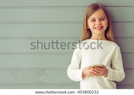 Portrait of pretty little girl in casual clothes holding a mobile phone, looking at camera and smiling, standing against gray background - stock photo