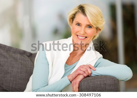 portrait of pretty middle aged woman sitting on sofa - stock photo