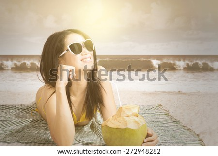 Portrait of pretty model lying on beach while wearing swimsuit and drinking a coconut water, shot with an instagram filter - stock photo