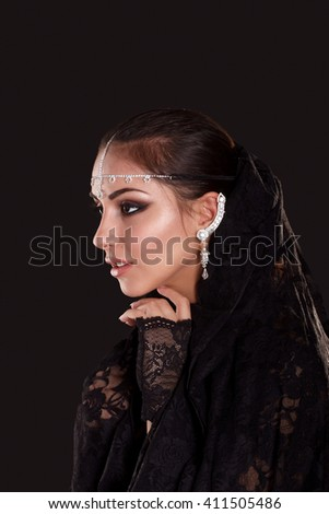 Portrait of Pretty oriental woman in abaya on black background