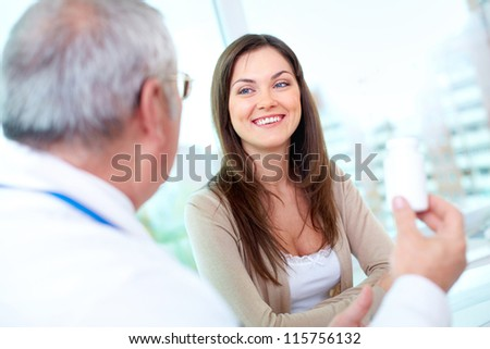 Portrait of pretty patient listening to mature practitioner in hospital - stock photo