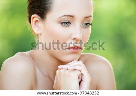 Portrait of pretty pensive young woman at summer green park - stock photo