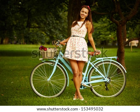 Portrait of pretty pinup girl with blue bicycle in retro style