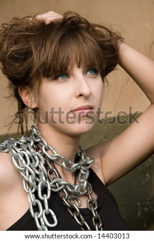 Portrait of pretty red-haired girl with a metal chain on the neck . - stock photo