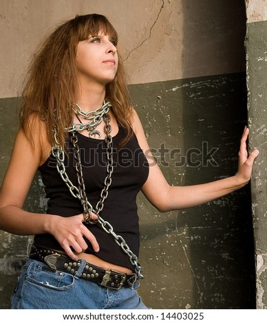 Portrait of pretty red-haired girl with a metal chain on the neck and shoulder . - stock photo