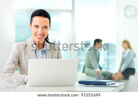 Portrait of pretty secretary looking at camera while working - stock photo