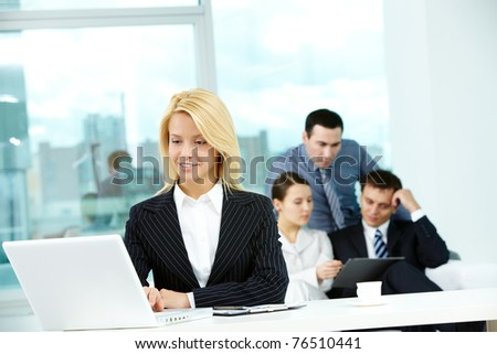 Portrait of pretty secretary looking at laptop screen in working environment - stock photo