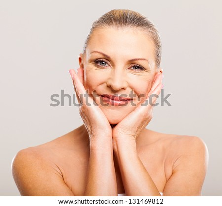 portrait of pretty senior woman with hands on her face - stock photo