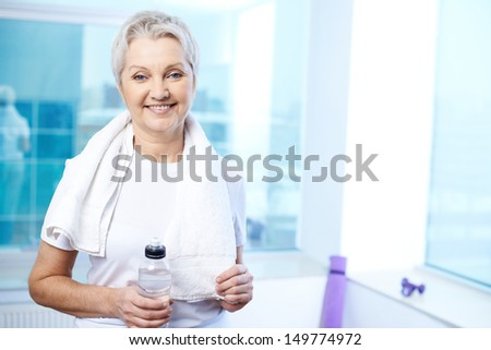 Portrait of pretty senior woman with towel and bottle of water in gym  - stock photo