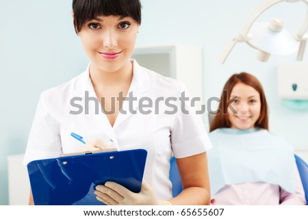 portrait of pretty smiley doctor with patient at dentist's office