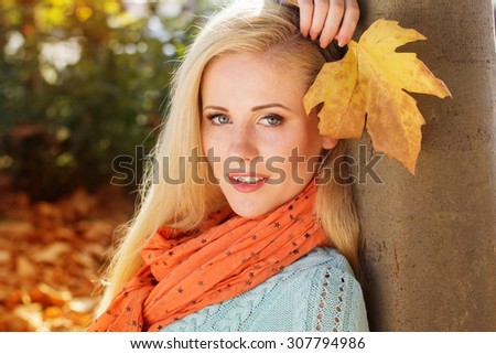 Portrait of pretty smiling blonde girl in autumn park with maple leaves is wearing mint color sweater - stock photo