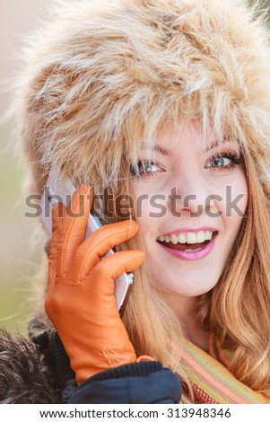 Portrait of pretty smiling fashionable woman talking on mobile phone. Happy gorgeous young girl in fur winter hat and jacket. Autumn fashion and communication.