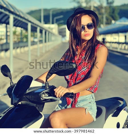 Portrait of pretty smiling girl on scooter - stock photo