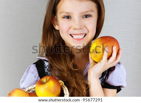 portrait of pretty, smiling, long-haired girl in dress holding wicker basket with apples on gray background - stock photo