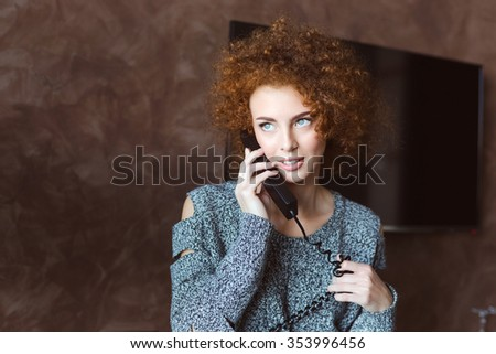 Portrait of pretty smiling redhead curly young female using telephone in hotel room - stock photo