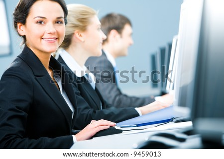 Portrait of pretty specialist sitting at the table and touching a computer mouse on the background of colleagues