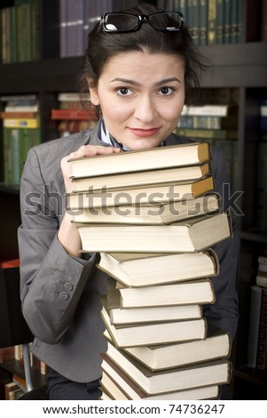 portrait of pretty student in library holding many books - stock photo