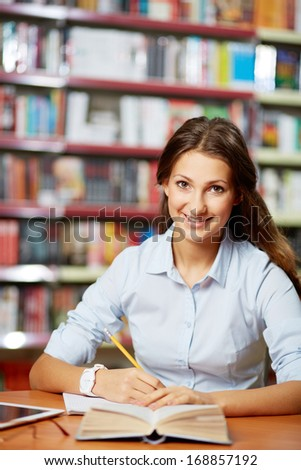 Portrait of pretty student looking at camera while working in college library - stock photo